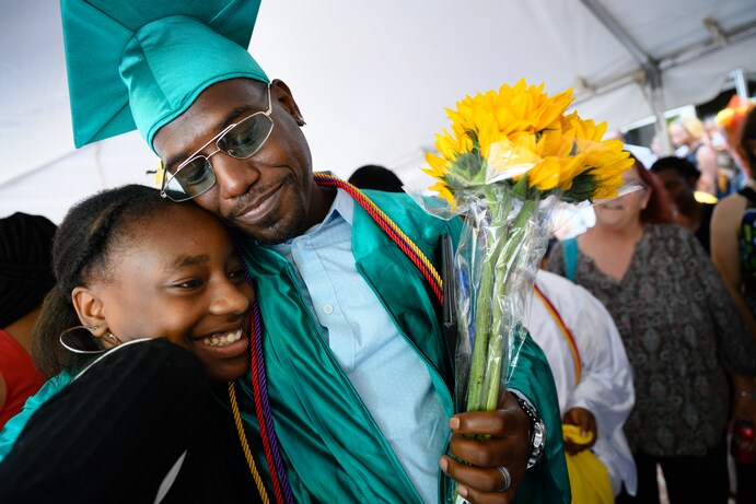 Stephen Corbin gets a congratulatory hug from his niece, Tiandra Prather, 15, after graduating from the Goodwill Excel Center. (Sarah L. Voisin/The  Washington Post)