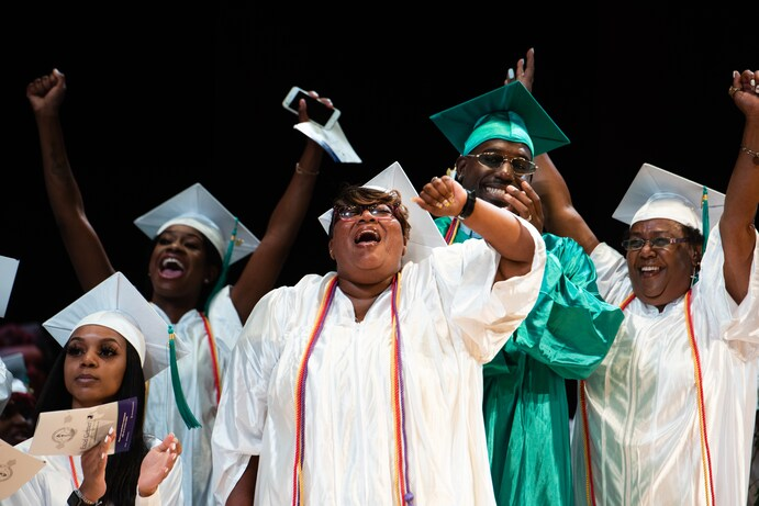 Danielle Corbin, 40, center, and her husband, Stephen Corbin, 33, next to her, cheer during their July 19 graduation from the Goodwill Excel Center, an adult public charter high school in Washington. (Sarah L. Voisin/The Washington Post)